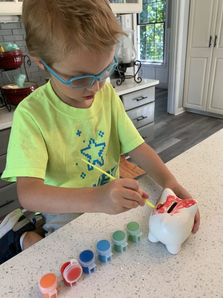 Painting his new piggy banks!